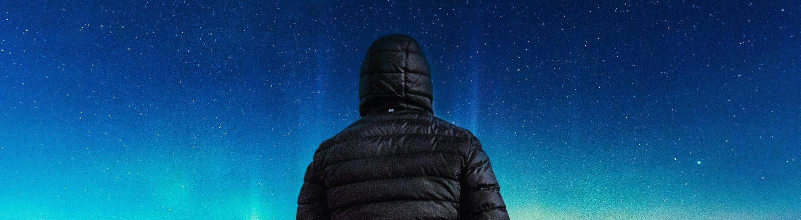 Rückenansicht einer Person, die in den Nachthimmel schaut.