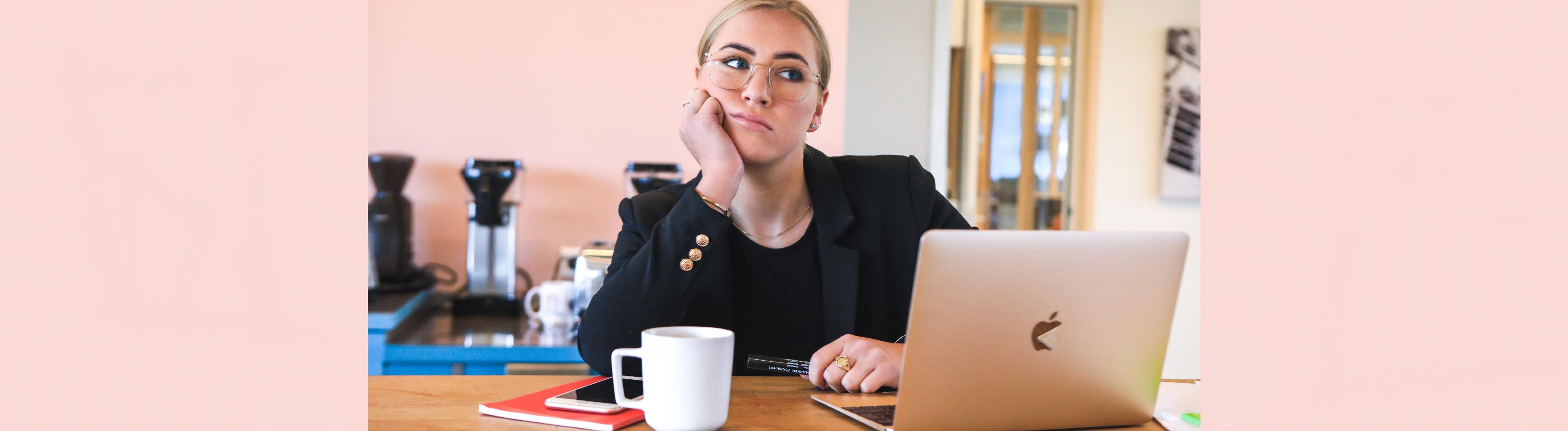 Frau sitzt grübelnd an einem Tisch vor Notebook.