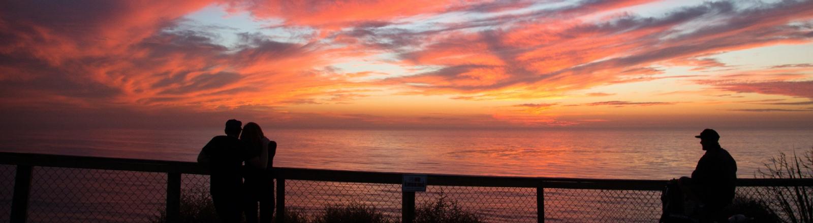 Drei Menschen beobachten einen Sonnenuntergang über dem Meer.
