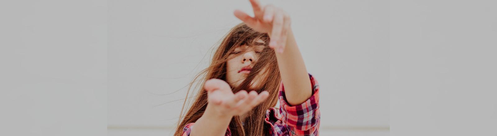 Eine junge Frau streckt ihre Arme mit geschlossenen Augen nach vorn aus.