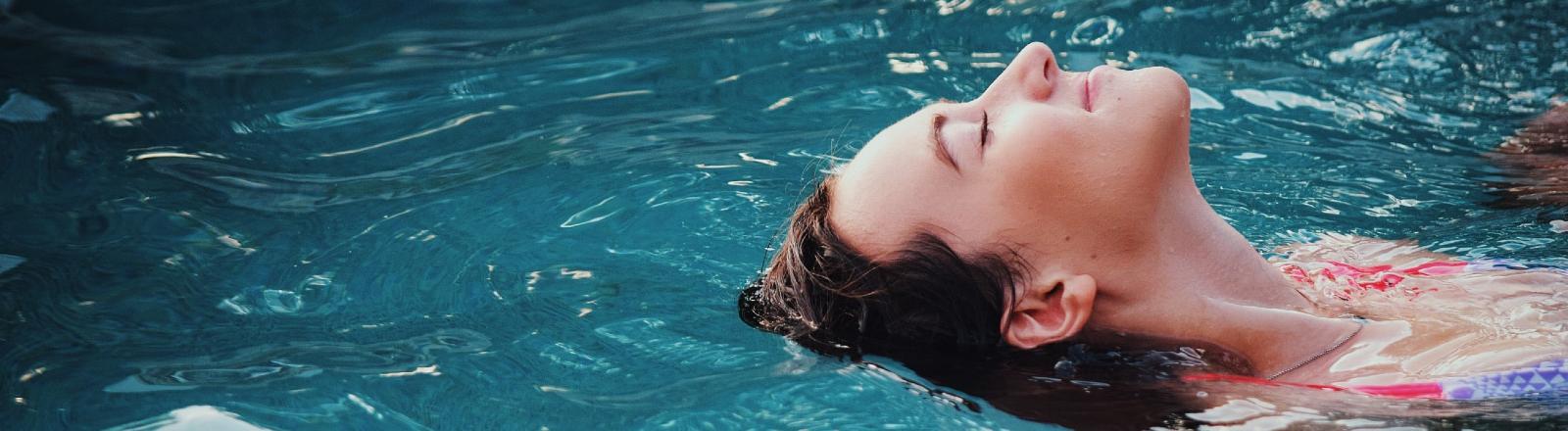 Frau treibt auf dem Rücken im Wasser.