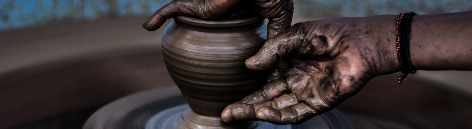 Zwei Hände töpfern ein Gefäß.
