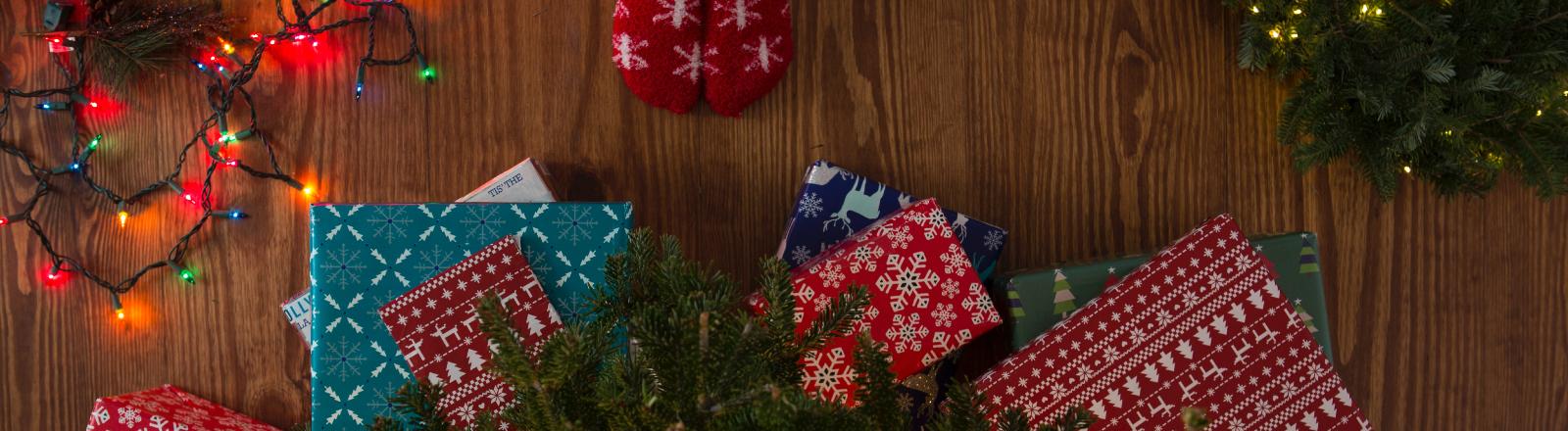 Weihnachtsgeschenke liegen auf dem Boden.