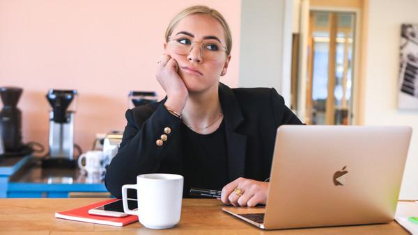 Frau sitzt grübelnd an einem Tisch vor einem Notebook.