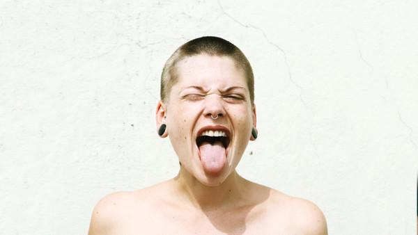 Frau streckt fröhlich ihre Zunge aus