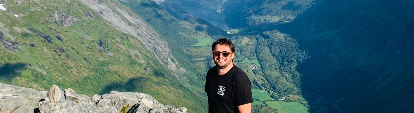 Der Reise-Fan Bernhard posiert auf einem Gebirgszug.