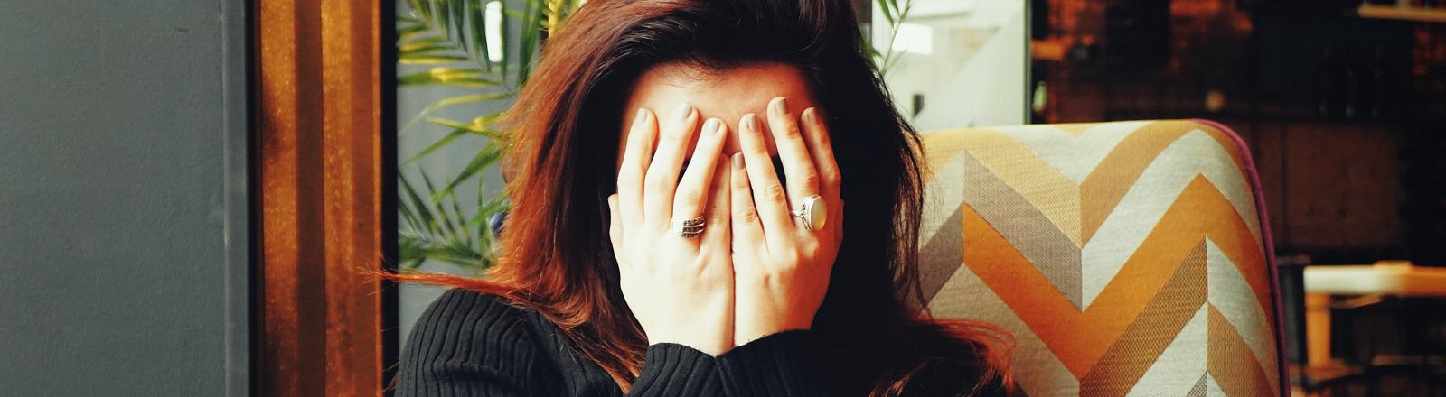 Eine Frau sitzt auf einem Sessel und versteckt das Gesicht unter den Händen.