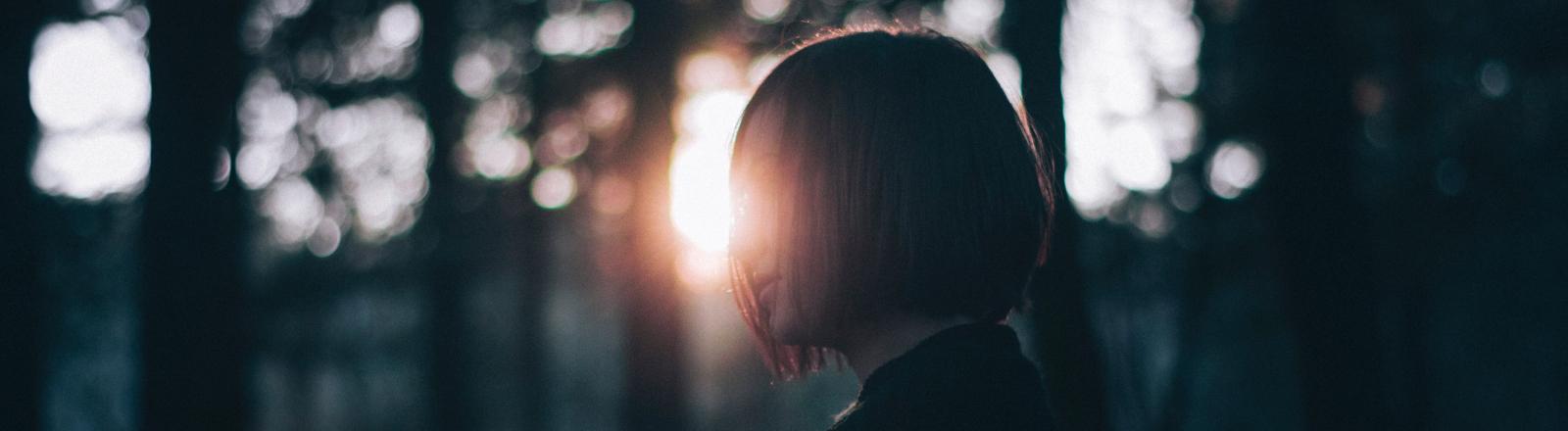 Eine Frau steht bei Sonnenruntergang in einem Wald.
