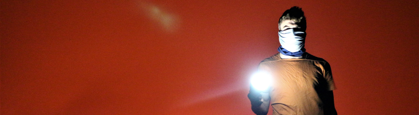 Person mit Maske und Taschenlicht steht vor rotem Abendhimmel.