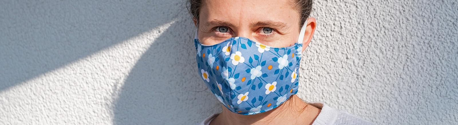 Symbolfoto zum Thema Corona-Pandemie, Covid-19 - Eine Frau traegt einen selbstgemachten Mundschutz aus Stoff und steht vor einer grauen Hausfassade, aufgenommen am 09.04.2020 in Leipzig.