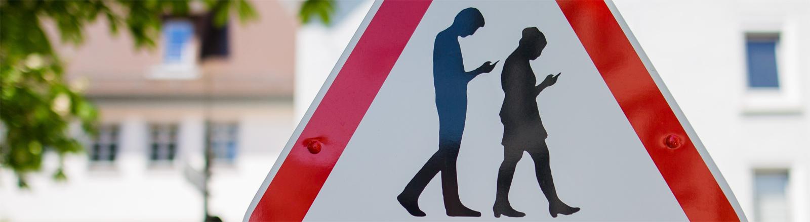 Ein Schild warnt neben einer Schule vor Menschen, die ständig mit dem Blick auf das Handy über die Straßen laufen.