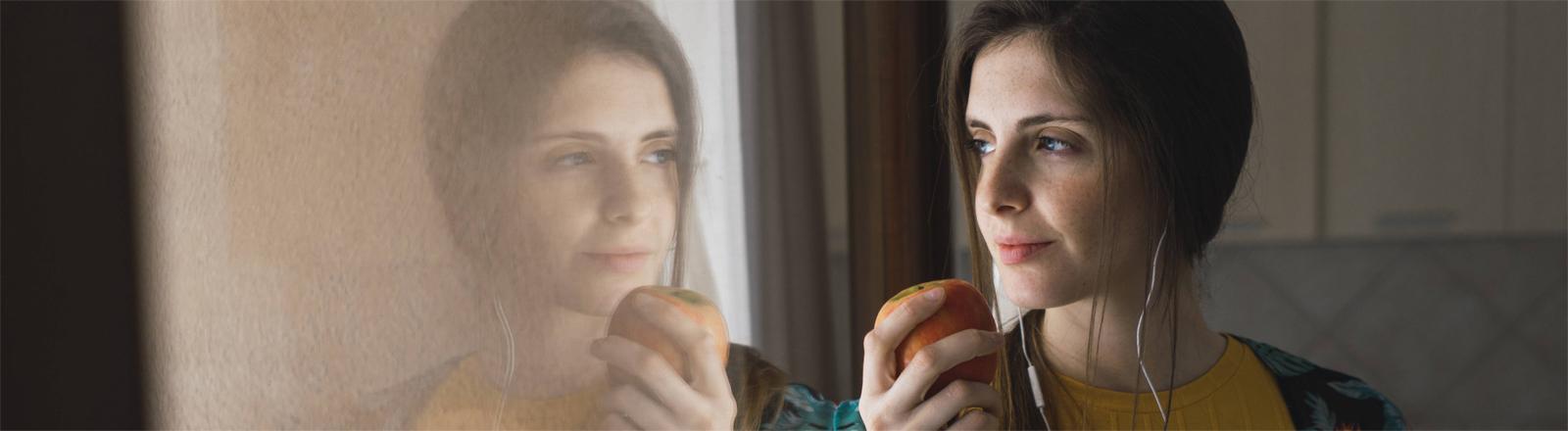 Eine musikhörende Frau isst einen Apfel