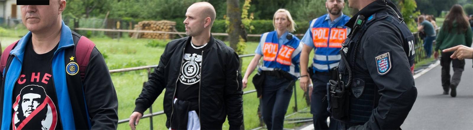 Mann mit Hakenkreuz auf T-Shirt wird von Thüringer Polizei im thüringischen Themar bei einem Nazi-Rockkonzert im Sommer 2017 abgefangen