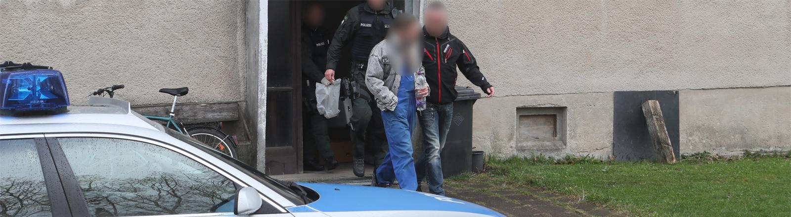 Polizeibeamte und ein sogenannter Reichsbürger kommen im April 2017 aus einem Wohnblock im thüringischen Gefell.