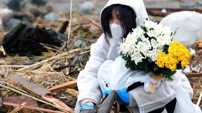 Eine Frau sitzt mit Atemschutzmaske inmitten von Trümmern und hält zwei Blumensträuße fest.