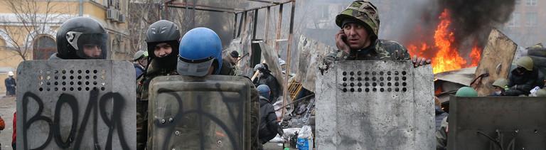 Eine kleine Gruppe von Demonstranten steht am 20.02.2014 in Kiew, einer von ihnen telefoniert.