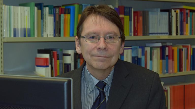 Der Politikwissenschaftler Uwe Jun sitzt am 9. Februar 2016 in Trier an seinem Büroschreibtisch