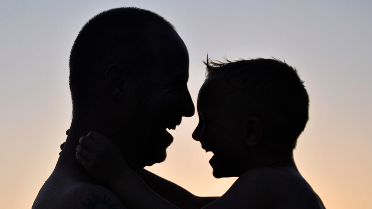 Ein Vater hält seinen Sohn auf dem Arm