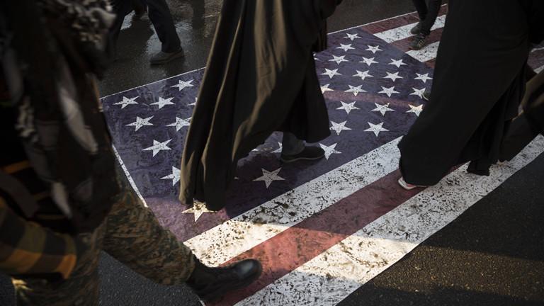 Füße gehen über eine amerikanische Flagge auf dem Boden.