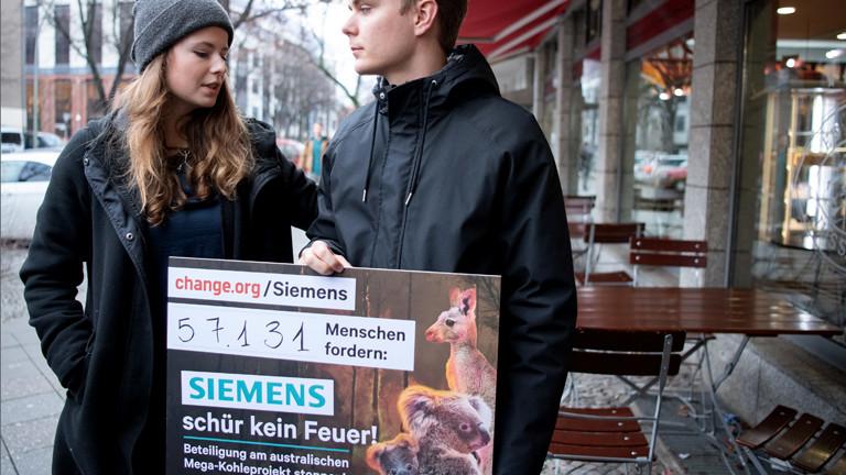 """Frau und Mann mit einem Plakat: """"Siemens, schür kein Feuer!"""""""