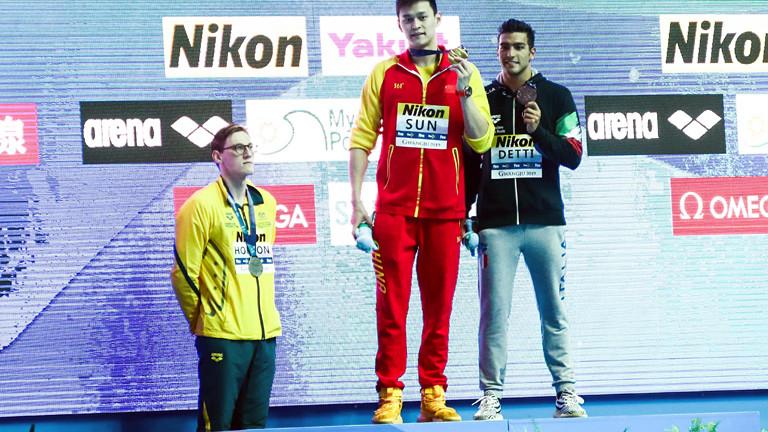 Schwimmer steht bei einer Siegerehrung neben dem Podest