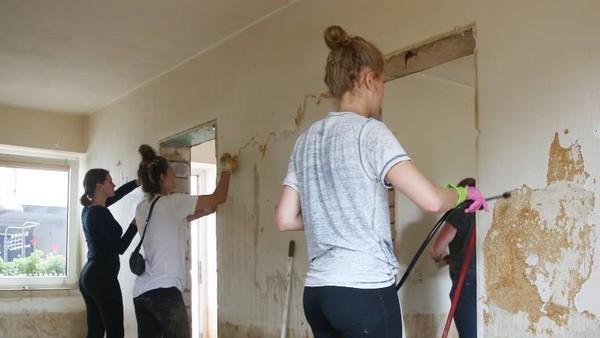 Drei junge Frauen entfernen Tapete aus einem von der Flut beschädigten Haus.
