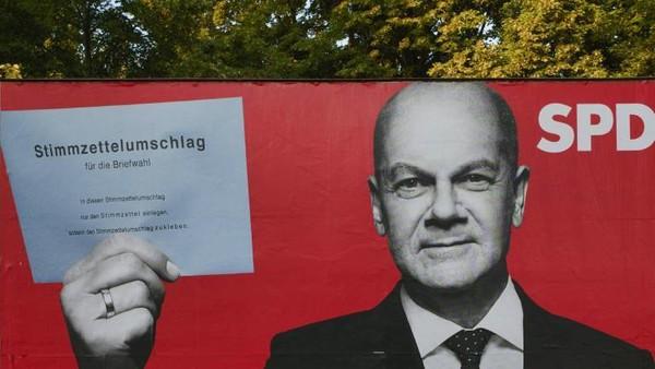 Ausschnitt eines Wahlplakates mit SPD-Kanzlerkandidat Olaf Scholz, der einen Stimmzettelumschlag hochhält