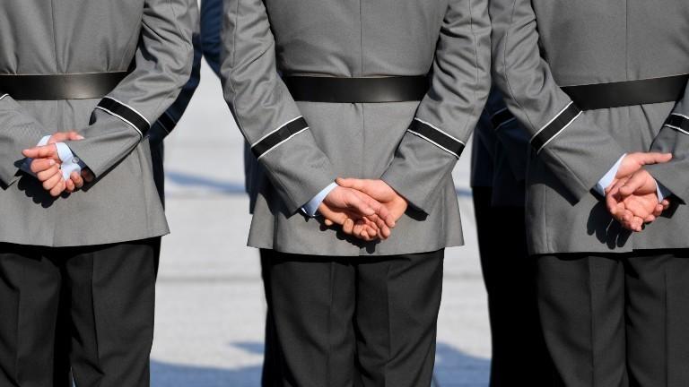 Soldaten, die die Hände hinter dem Rücken verschränkt halten.
