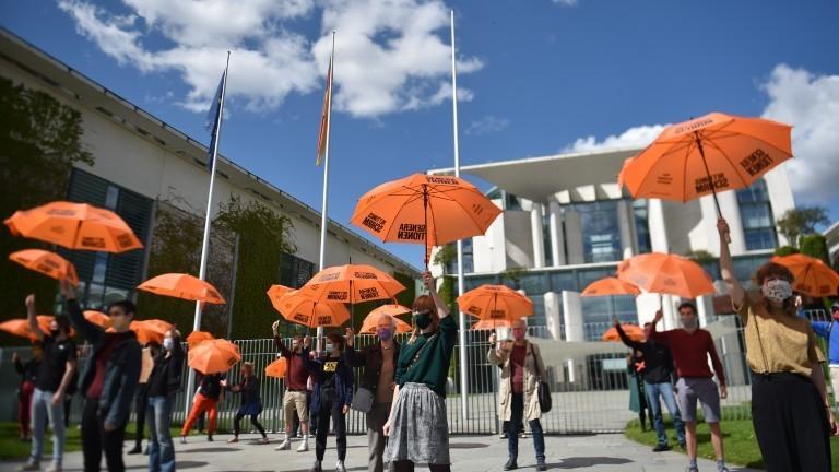 """Demonstranten halten zum Auftakt der Kampagne """"Generationen-Rettungsschirm"""" der Generationen Stiftung Regenschirme vor dem Kanzleramt."""