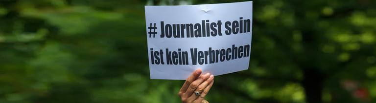 """""""Journalist sein ist kein Verbrechen"""" steht am 21.06.2015 in Berlin auf einem Papier, das eine Frau vor einer Polizeistation hält, um für die Freilassung des Al Jazeera-Journalisten Ahmed Mansour zu demonstrieren."""
