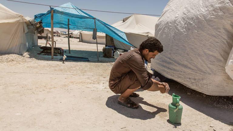 Ein Mann kniet in einem syrischen Flüchtlingscamp am Boden und wäscht sich die Hände.