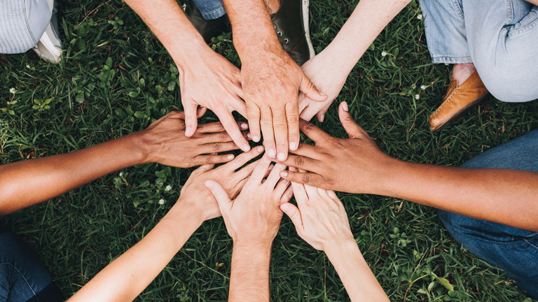 Menschen verschiedener Hautfarbe halten ihre Hände übereinander.