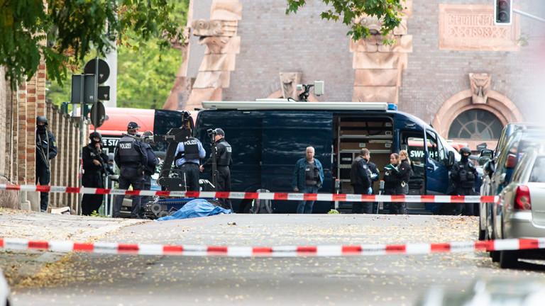 09.10.2019, Sachsen-Anhalt, Halle: Polizisten sichern an der Mauer zur Synagoge die Umgebung, eine abgedeckte Leiche liegt auf der Straße.