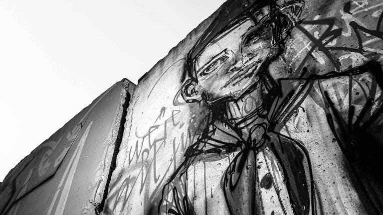 Berliner Mauer mit Graffiti von einem Jungen