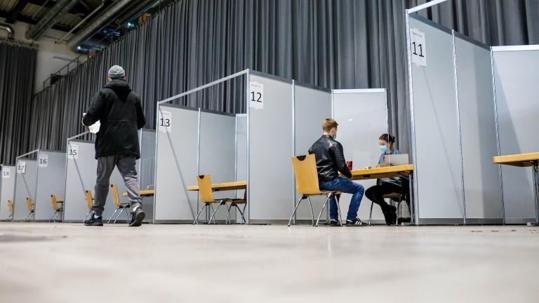 Studierende sitzen und gehen während eines Probelaufs im Registrierungsbereich des Zentralen Impfzentrum an der Freiburger Messe.