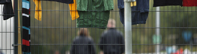 Sicherheitskräfte (hinten) laufen auf dem Gelände des Flüchtlingsheim der ehemaligen Siegerland-Kaserne am 29.09.2014 in Burbach (Nordrhein-Westfalen) während Wäsche zum Trocknen über einem Zaun hängt.