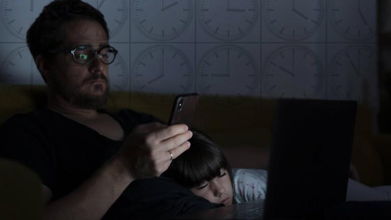 Arbeiten statt Pause: Mann blickt prüfend auf sein Handy