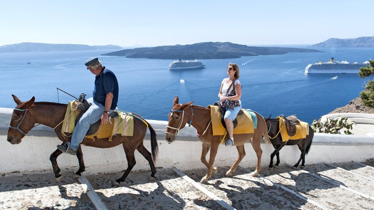 Eselguide, Touristin und drei Esel auf der griechischen Insel Santorin