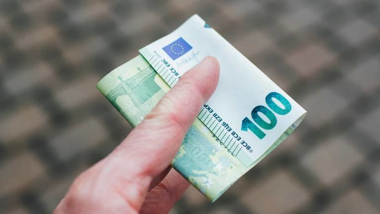 Ein 100-Euro-Schein ist zwischen zwei Fingern geklemmt.