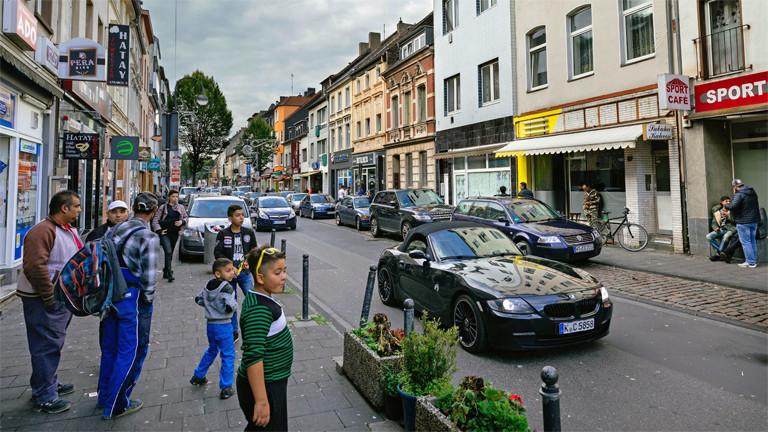 Eine Straße mit Autos und Menschen.