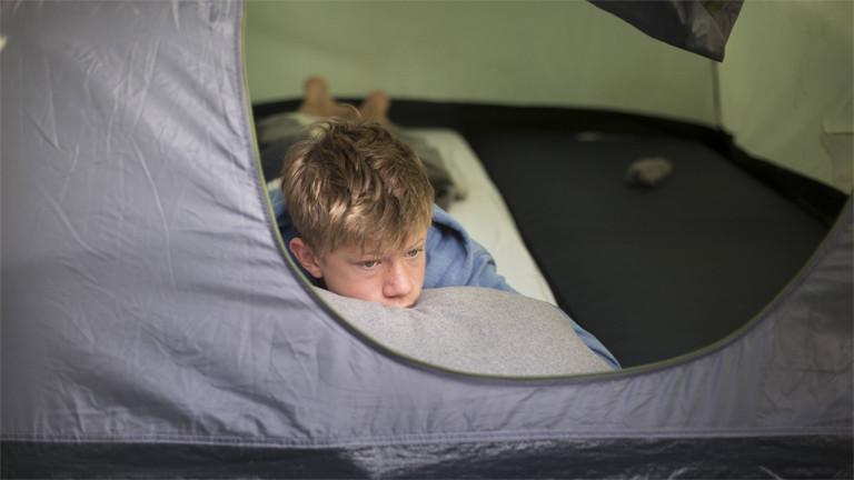 Unser Symbolbild zeigt einen Jungen der im August 2018 aus einem Zelt in Dülmen guckt