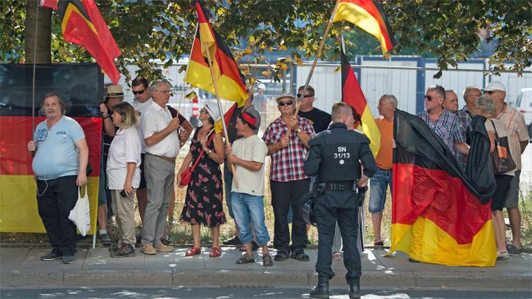 Pegidademonstranten und ein Polizist am 16. August in der sächsischen Landeshauptstadt Dresden
