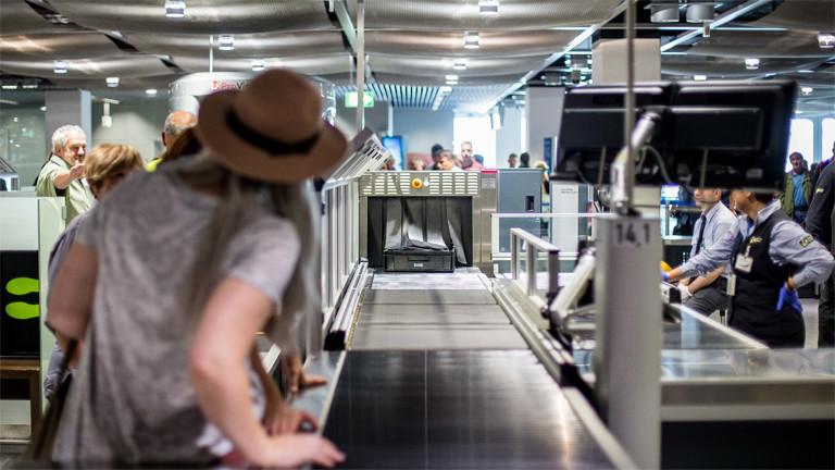Eine Frau steht im Juli 2016 am Flughafen Düsseldorf bei der Sicherheitskontrolle.