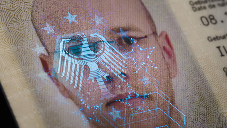 Auf dem Biometrischen Passfoto eines Personalausweises spiegelt sich ein Bundesadler als Hologramm.