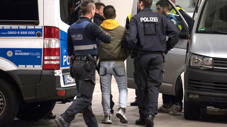 Polizisten führen einen Mann ab