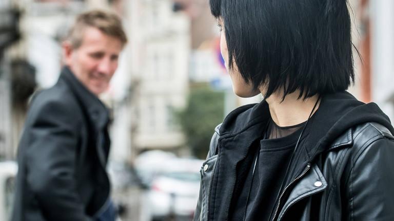 Mann dreht sich auf der Straße um zu einer Frau.