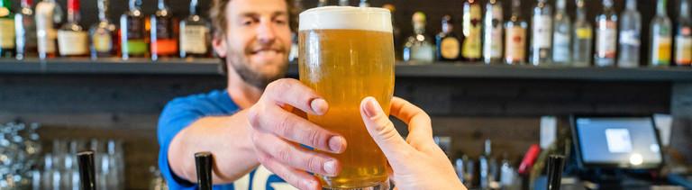 Barkeeper reicht ein Bier