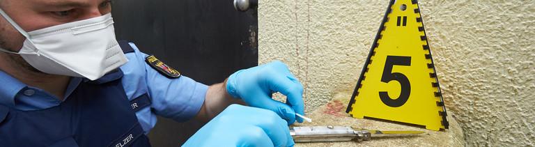 Ein Polizist nimmt DNA-Proben
