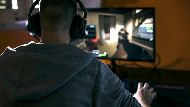 Mann sitzt vor einem Rechner und spielt Computerspiele