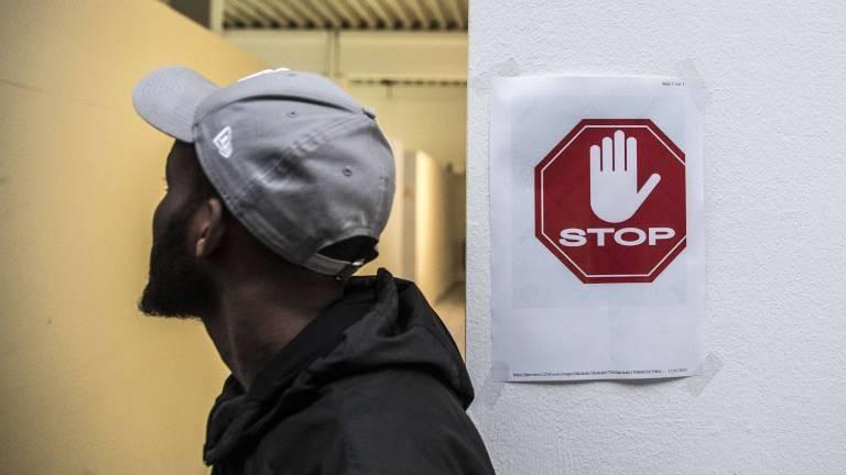 Schwarzer Mann vor einem Stop-Zeichen